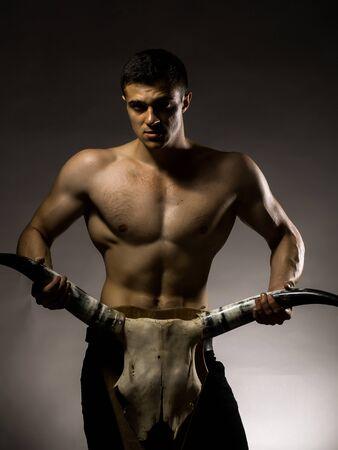 nackte brust: Junger stattlicher Mann mit muskul�sen K�rper nackte Brust und Rumpf posiert im Studio auf grauem Hintergrund Tier Sch�del mit Geweih halten