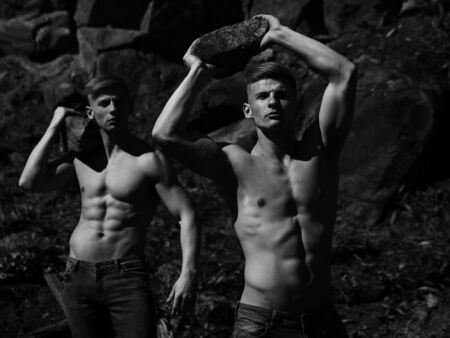 muscular body: Strong men young handsome twins with sexy muscular body bare torso hold stones black and white on mountain background