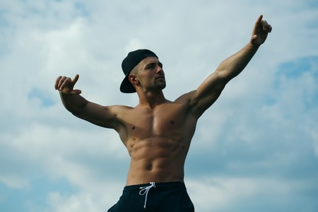 bare chest: young macho man model athlete with muscular sexy body and bare chest posing outdoor on sky background