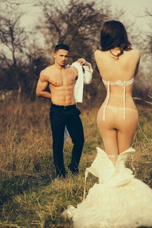 Young happy wedding couple of pretty woman and man undressing in field outdoor
