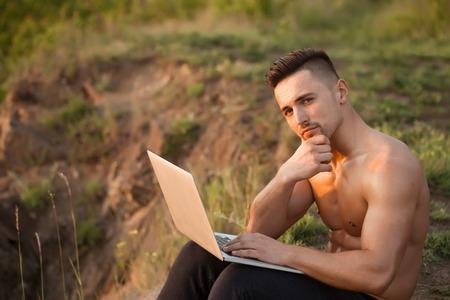 nackte brust: Junger stattlicher Mann mit dem muskul�sen sexy K�rper und nackte Brust mit dem Laptop im Freien sonnigen Tag sitzt