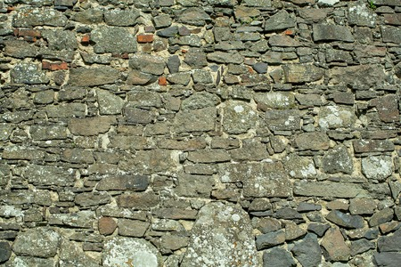 uneven: Stone wall grey uneven cracked surface on rock background