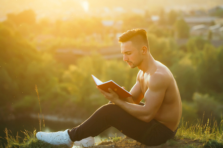 bare chest: Young handsome man with muscular sexy body and bare chest sitting with book outdoor sunny day