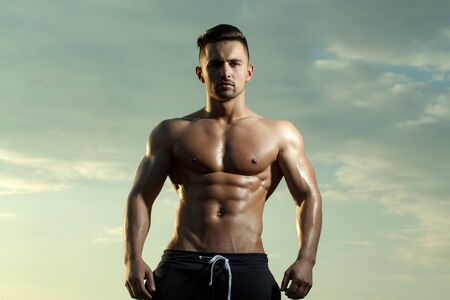 bare chest: young macho man model athlete with muscular sexy body and wet bare chest outdoor on sky background