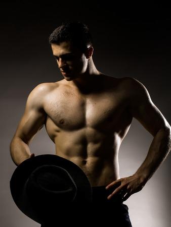 nackte brust: Junger stattlicher Mann mit muskulösen Körper mit Hut mit nacktem Oberkörper und Rumpf auf grauem Hintergrund im Studio aufwirft
