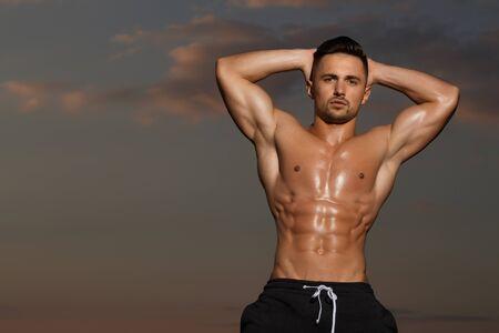 nackte brust: jungen Macho-Mann-Modell Athlet mit muskulösen sexy Körper und nassen nackten Brust im Freien am Himmel im Hintergrund