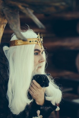 wiccan: Druid old man with long grey hair and beard with crown in fur coat holds cat on dark wooden background