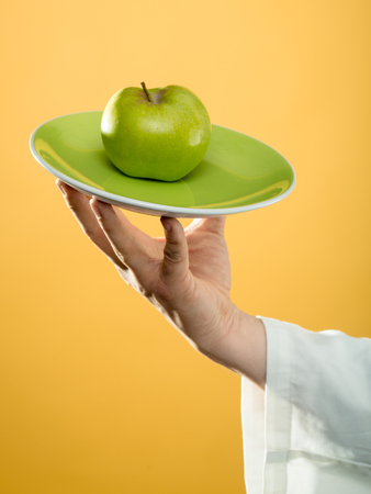 white sleeve: green apple on plate in human hand of young chef in white sleeve on yellow background