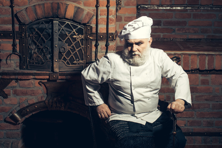 sits: Senior male chief cook bearded man in uniform and hat sits at oven on kitchen background