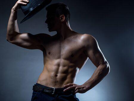 nackte brust: Junger stattlicher Mann mit muskul�sen K�rper mit Hut mit nacktem Oberk�rper und Rumpf auf grauem Hintergrund im Studio aufwirft