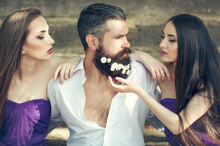 hombre guapo en camisa blanca con flores de diente de león en la barba con dos mujeres muy jóvenes en vestidos de color violeta en las escaleras de piedra al aire libre día soleado