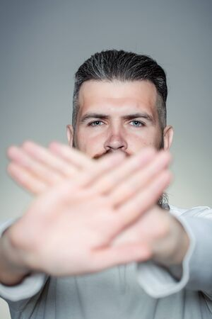 long beard: handsome young man with long beard and moustache on face holding hands in stop gesture on grey background in studio