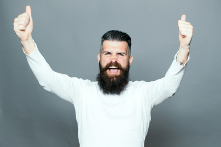 long beard: handsome young man with long beard and moustache on happy face with super gesture showing thumb up on grey background in studio