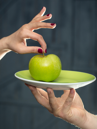 white sleeve: green apple on plate in human hands of young chef in white sleeve on wooden background