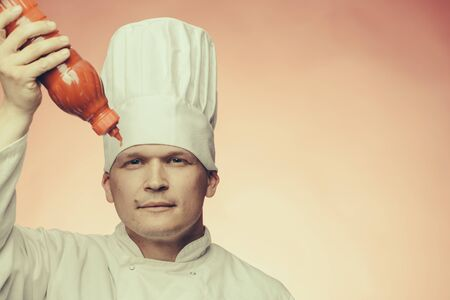 catsup: Young chef with red ketchup plastic bottle in white uniform and cook hat on studio background Stock Photo