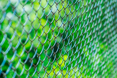metallized: Old wire security fence rusty metallized on sunny day on blurred green background