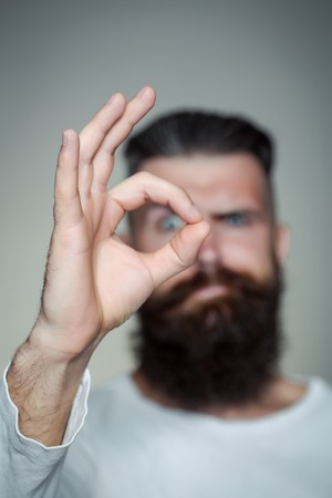 long beard: handsome young man with long beard and moustache on face with okey gesture of finger on grey background in studio
