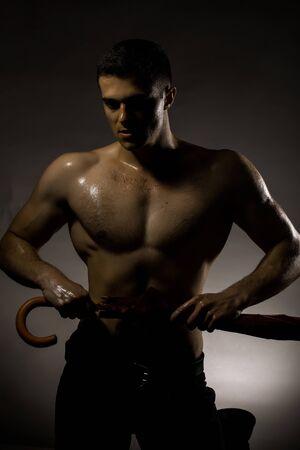 nackte brust: Junger stattlicher Mann mit muskul�sen K�rper nass nackte Brust und Rumpf posiert im Studio Regenschirm auf grauem Hintergrund Lizenzfreie Bilder