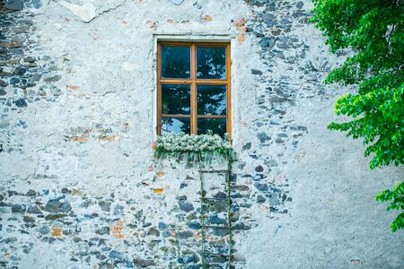 brick: Rope wooden stairs on white building brick wall with window and flowers outdoor on fairy background