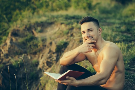 nackte brust: Young handsome smiling man with muscular sexy body and bare chest sitting with book outdoor sunny day