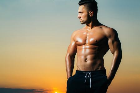 nackte brust: jungen Macho-Mann-Modell Athlet mit muskul�sen sexy K�rper und nassen nackten Brust im Freien am Himmel im Hintergrund