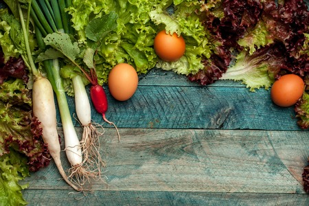 gallina con huevos: cebollas de primavera rojo r�bano blanco lechuga de hojas verdes y h�medos huevos de gallina frescos en el fondo mesa de madera Foto de archivo