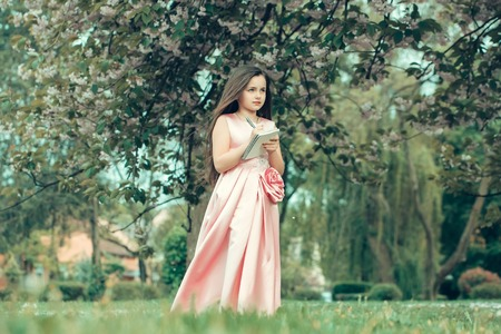 glamour girl: Pretty little girl poetess in glamour dress with long brunette hair writing in notebook with pen in spring pink flower blossom outdoor