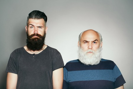 raised eyebrow: Old and young bearded men with long beard white and brown and raised eyebrow in studio on grey background