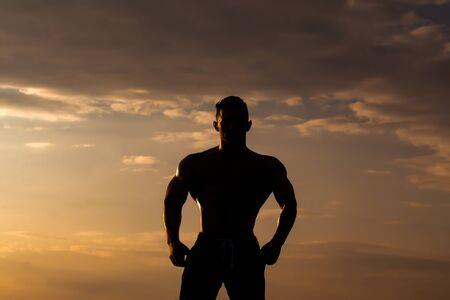 nackte brust: jungen Macho-Mann-Modell Athlet Silhouette mit muskul�sen sexy K�rper und nackten Brust im Freien am Himmel im Hintergrund