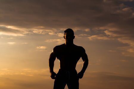 bare chest: young macho man model athlete silhouette with muscular sexy body and bare chest outdoor on sky background