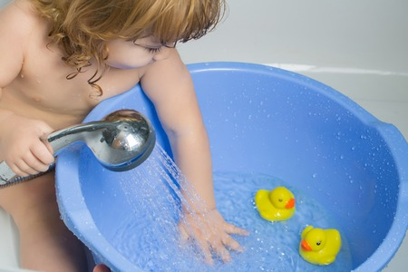 yellow duckling: Small cute funny baby boy with blonde hair playing with rubber yellow duckling toy in bath water