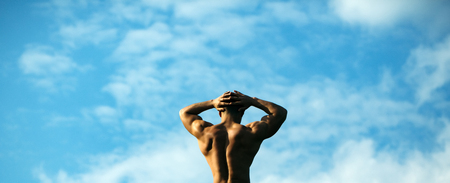 back posing: young macho man model athlete with muscular sexy body and bare back posing outdoor on sky background