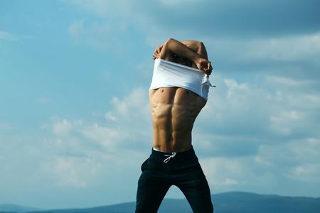 nackte brust: jungen Macho-Mann-Modell Athlet mit muskul�sen sexy K�rper und nassen nackten Brust im Freien am Himmel Hintergrund Auskleiden wei�es Hemd
