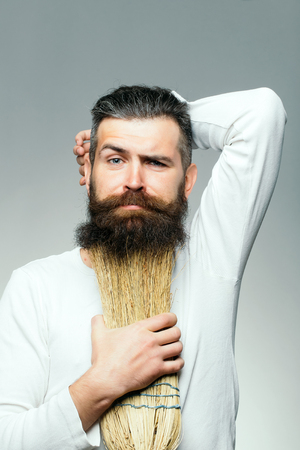besom: Bearded man with grimace face in white shirt holding broom as beard in studio on grey background