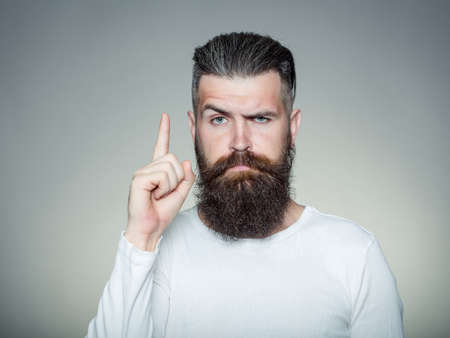 long beard: handsome young man with long beard and moustache on face with raised finger on grey background in studio Stock Photo