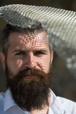 long beard: handsome young man with long beard and moustache on serious face with metallic net sunny day outdoor Stock Photo