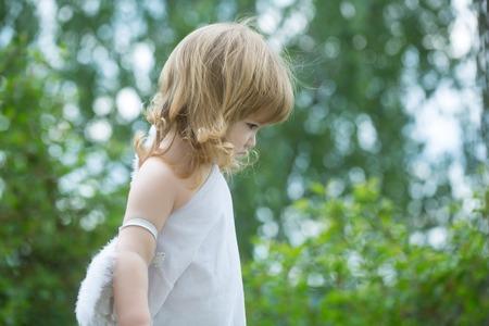 baby angel: piccolo ragazzo carino bambino con i capelli lunghi biondi in bianco di piume e ali d'angelo panno all'aperto su sfondo verde naturale