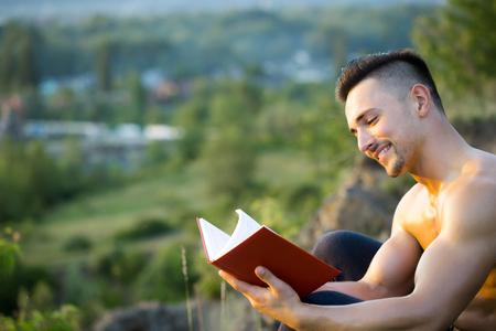 nackte brust: Junger stattlicher l�chelnder Mann mit dem muskul�sen sexy K�rper und nackte Brust mit Buch im Freien sonnigen Tag sitzt Lizenzfreie Bilder