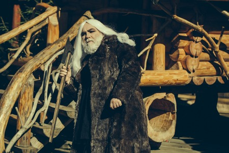 druid: Brutal druid old man with long silver hair and beard in fur coat with axe in hand on log house background Stock Photo