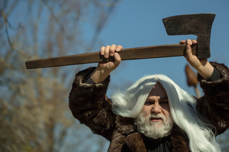 druid: Brutal druid old man with long silver hair and beard in fur coat with axe in hand on blue sky background Stock Photo