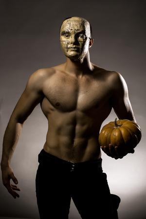 nackte brust: Junger stattlicher Mann in der Maske der Zeitung mit muskul�sen K�rper nackte Brust und Rumpf posiert im Studio auf grauem Hintergrund gelb Halloween-K�rbis halten