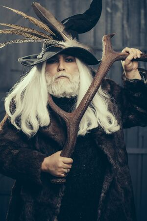 druid: Druid old man with long grey hair beard in hunter hat with bird feathers and fur coat with deer antlers in hands on dark background Stock Photo