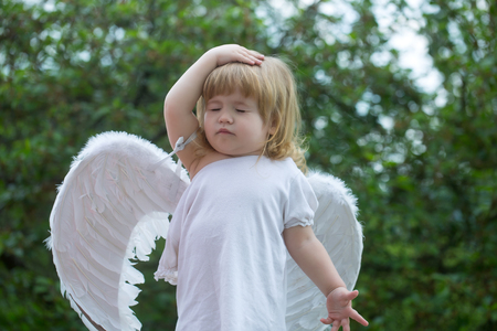 feathered: small cute baby boy with blonde long hair in white feathered angel wings and cloth outdoor on green natural background
