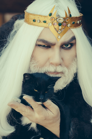 wiccan: Druid old man with long grey hair and beard with crown in fur coat holds cat on dark background Stock Photo