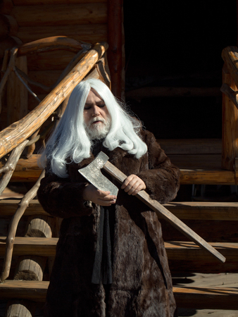 log house: Old man druid with long silver hair and beard in fur coat stands with axe on log house background