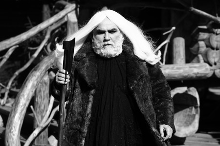 log house: Brutal druid old man with long silver hair and beard in fur coat with axe in hand black and white on log house background Stock Photo