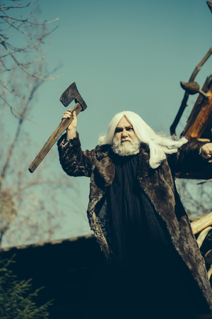 silver hair: Brutal druid old man with long silver hair and beard in fur coat with axe in hand on blue sky background Stock Photo