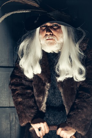hair feathers: Druid old man with long grey hair beard in hunter hat with bird feathers and fur coat leans on deer antlers on dark background