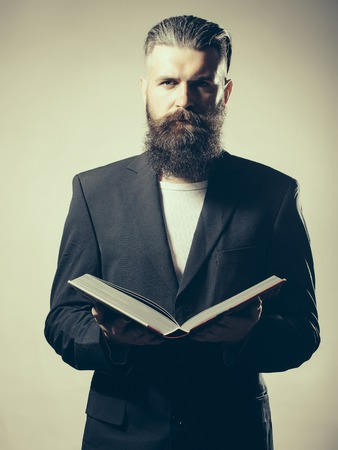book jacket: Handsome young man with long beard and moustache in black jacket holding open book in studio on grey background