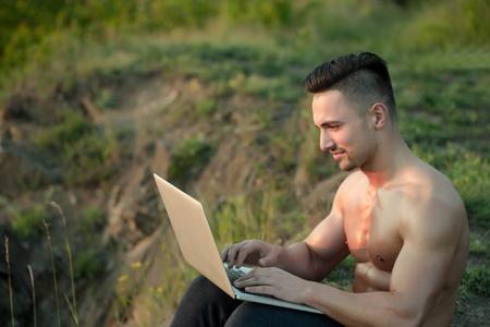 nackte brust: Junger stattlicher Mann mit dem muskulösen sexy Körper und nackte Brust mit dem Laptop im Freien sonnigen Tag sitzt